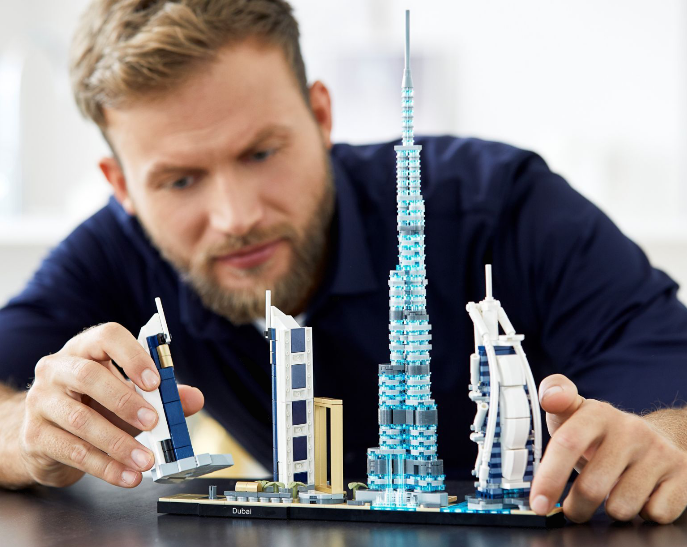 Adult building Dubai skyscrapers with LEGO bricks