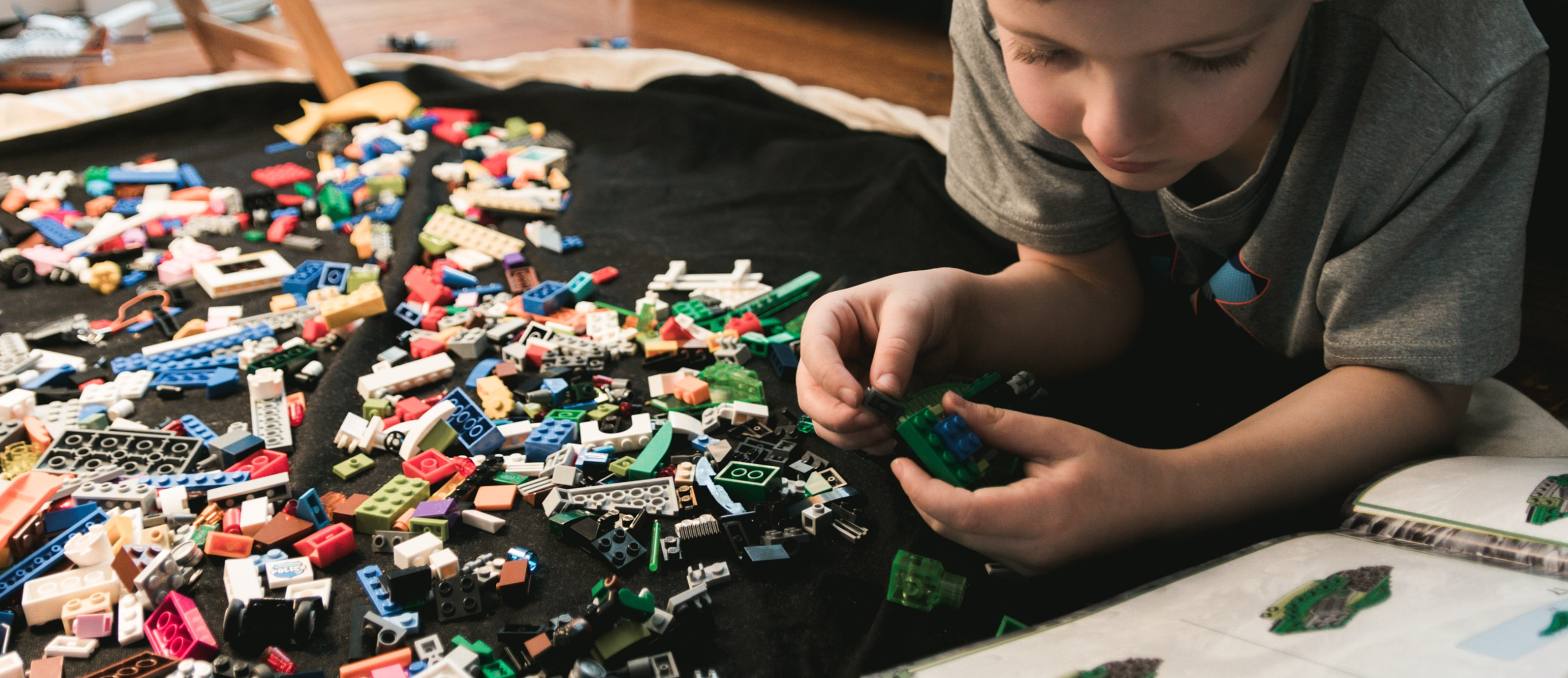 Child playing on the floor with numerous LEGO bricks