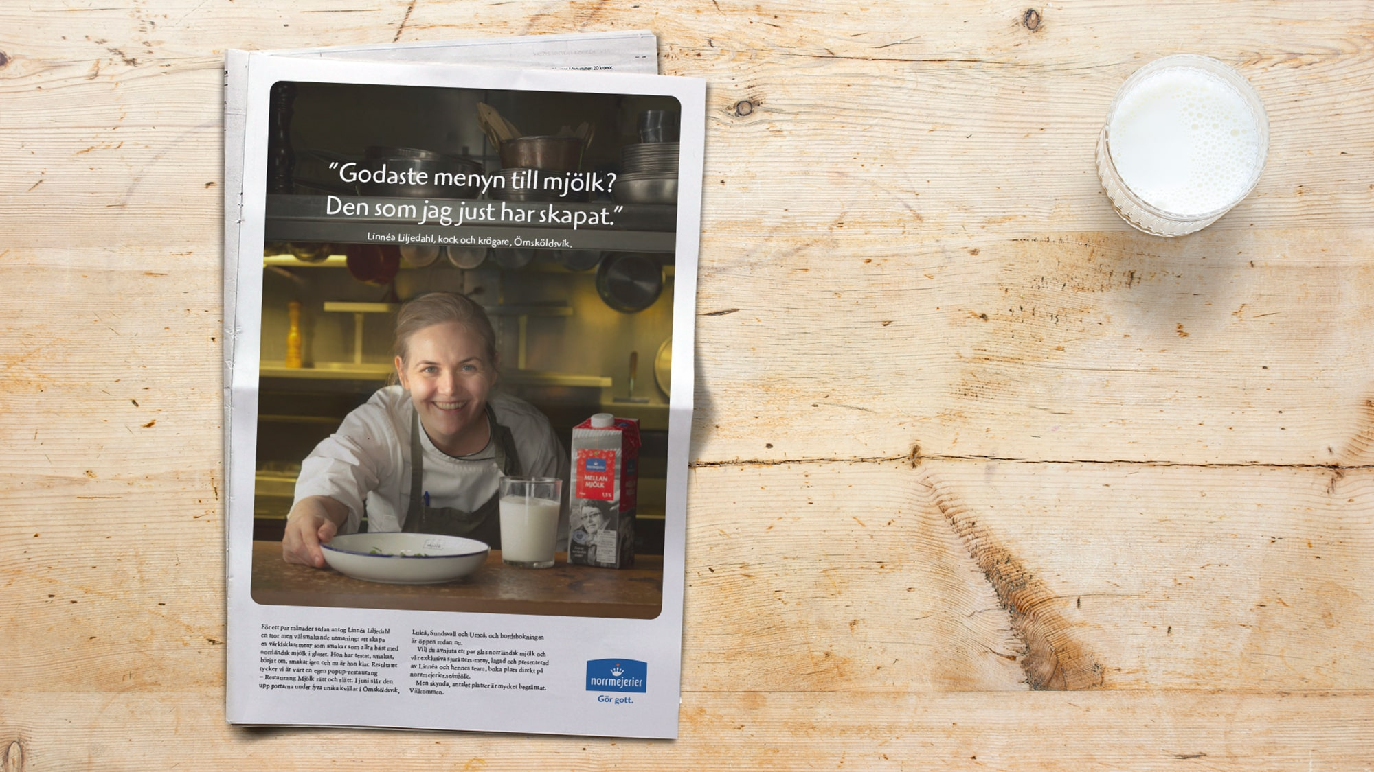 Newspaper with an ad for Milk put on wooden table with glass of milk